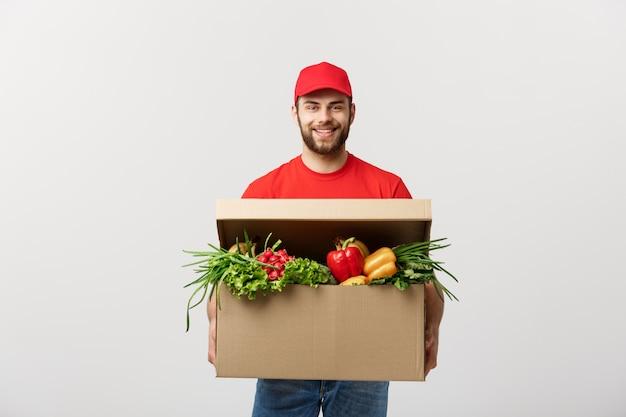 Kaukaski kurier dostawy kurier człowiek w czerwonym mundurze z pole spożywcze ze świeżymi owocami