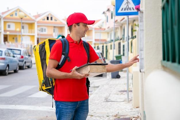 Kaukaski kurier przewożący paczkę i dzwoniący do drzwi przy dostawie do domu. dostarczyciel w średnim wieku z żółtą torbą termiczną stojący przed domem. usługa dostawy i koncepcja poczty