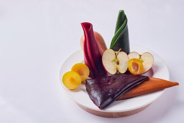 Kaukaski lawasz owocowy w białym talerzu z jabłkiem i śliwkami.