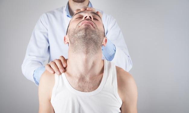 Kaukaski lekarz masuje głowę pacjenta