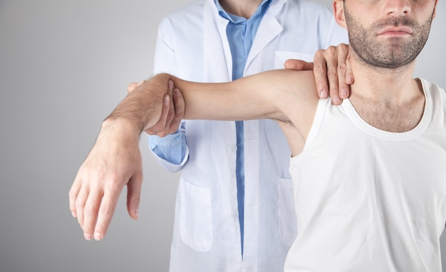 Kaukaski lekarz masuje ramię pacjenta