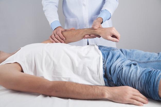 Kaukaski lekarz masuje rękę pacjenta.