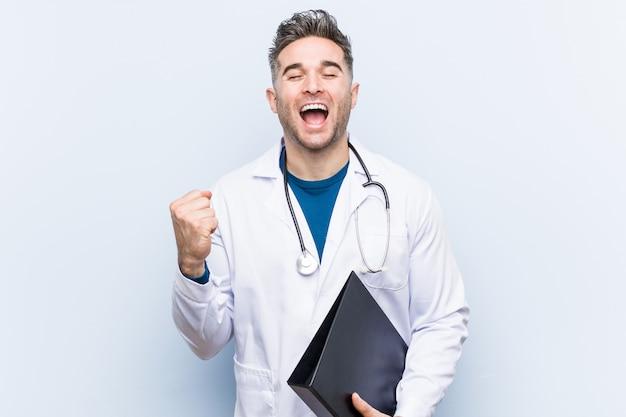 Kaukaski lekarz mężczyzna trzyma folder doping beztroski i podekscytowany.