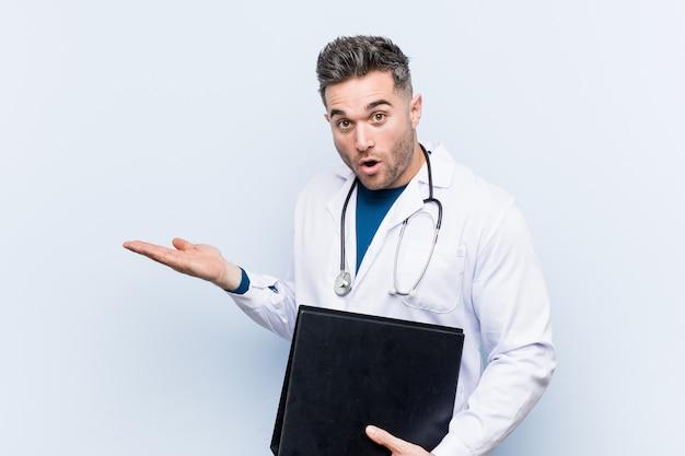 Kaukaski lekarz mężczyzna trzyma folder pod wrażeniem, trzymając kopię miejsca na dłoni.
