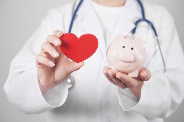 Kaukaski lekarz pokazując czerwone serce i skarbonkę.