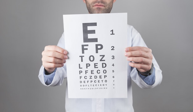 Kaukaski lekarz pokazujący badanie wzroku.