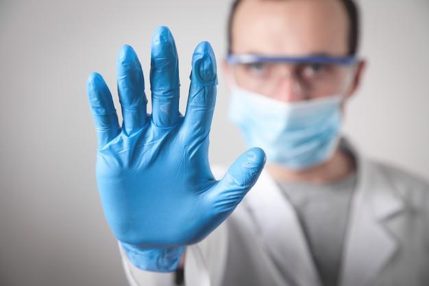 Kaukaski lekarz robi gest stopu.