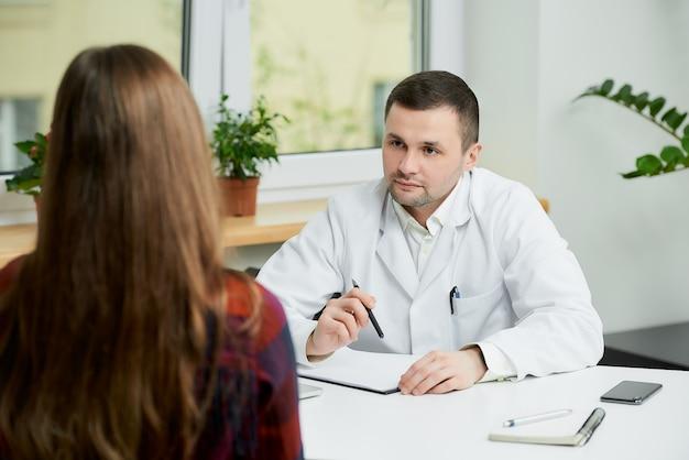 Kaukaski lekarz w białym fartuchu siedzi przy biurku i słuchając pacjenta