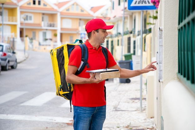 Kaukaski listonosz trzymający paczkę i dzwoniący dzwonek do drzwi. widok z boku pracownika urzędu pocztowego w średnim wieku w czerwonym mundurze, dostarczając zamówienie do klienta i stojąc na zewnątrz. usługa dostawy i koncepcja poczty