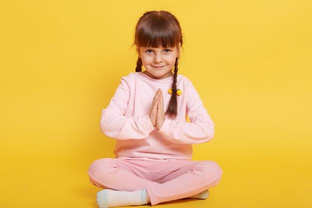 Kaukaski mała ciemnowłosa dziewczyna patrzy na kamerę z nieśmiałym uśmiechem