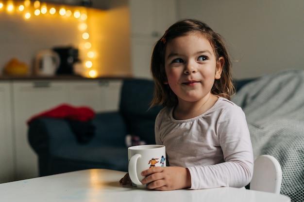 Kaukaski maluch dziewczyna pije kakao z kubka w domu. boże narodzenie światła bokeh. wysokiej jakości zdjęcie