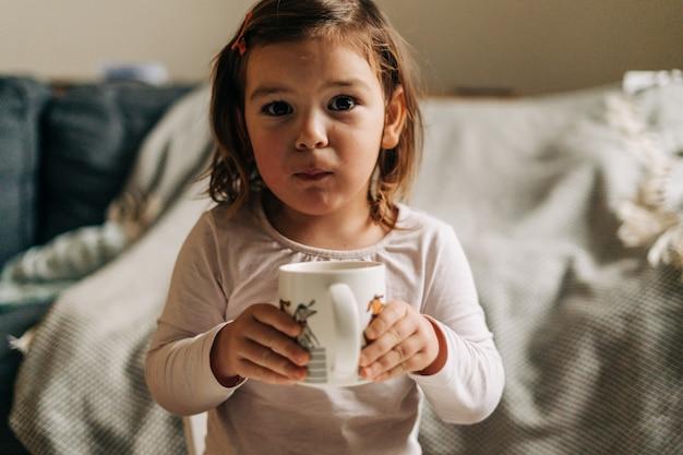 Kaukaski maluch dziewczyna pije kakao z kubka w domu. boże narodzenie światła bokeh