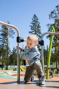 Kaukaski mały chłopiec samodzielnie wspina się na zjeżdżalnię, aby zjechać na placu zabaw na świeżym powietrzu w słoneczny dzień.