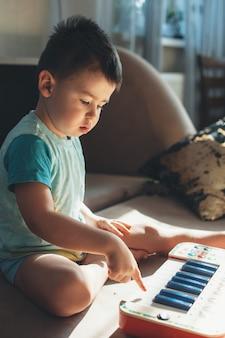 Kaukaski mały dzieciak próbuje grać na pianinie na podłodze