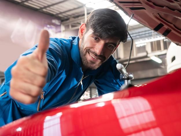 Kaukaski mechanik samochodowy w mundurze pracy w garażu. lista kontrolna technika naprawy maszyny samochód w garażu.