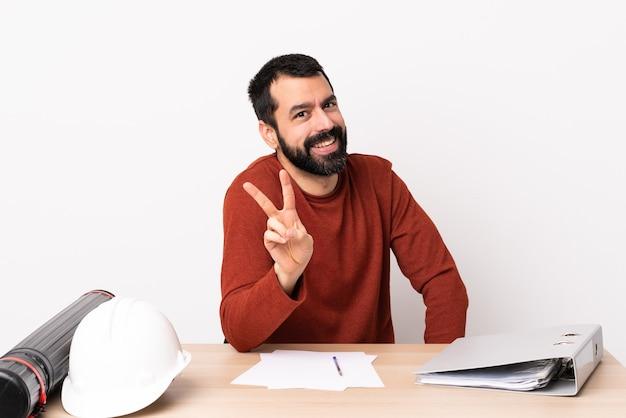 Kaukaski mężczyzna architekt z brodą w tabeli uśmiechnięty i przedstawiający znak zwycięstwa.