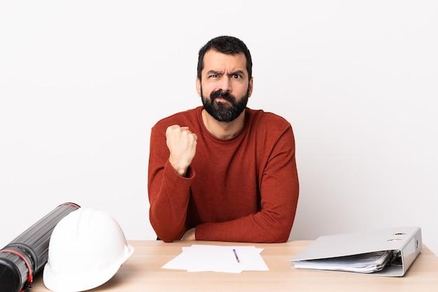 Kaukaski mężczyzna architekt z brodą w tabeli z nieszczęśliwym wyrazem twarzy.