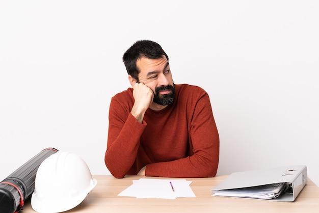 Kaukaski mężczyzna architekt z brodą w tabeli z wyrazem zmęczony i znudzony.