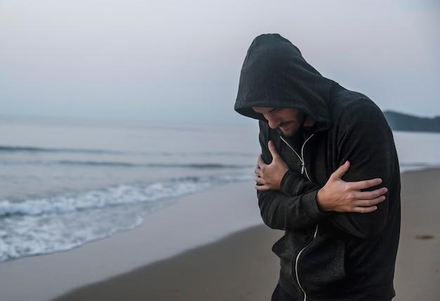 Kaukaski mężczyzna chodzi samotnie przy plażą