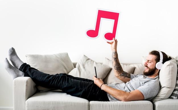 Kaukaski mężczyzna cieszy się muzykę trzyma muzyczną nutową czas wolny i muzyki pojęcie w domu