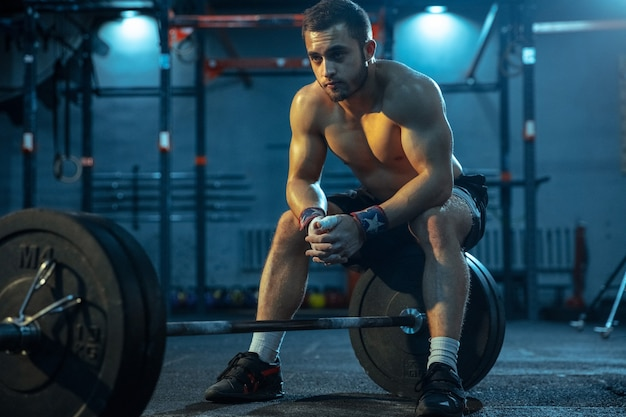 Kaukaski mężczyzna ćwiczący w podnoszeniu ciężarów na siłowni kaukaski męski model sportowy