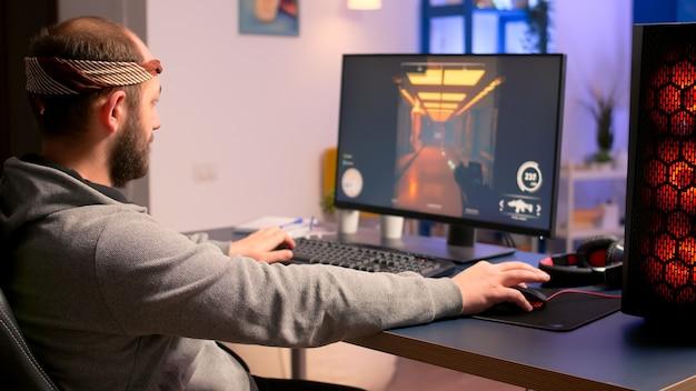 Kaukaski mężczyzna grający w gry wideo online o wirtualne mistrzostwa przy użyciu profesjonalnego pulpitu systemu rgb. profesjonalny gracz siedzący na fotelu do gier, patrzący i uśmiechający się do kamery późno w nocy w domowym studio.
