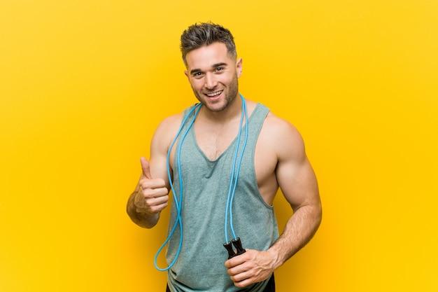 Kaukaski mężczyzna holdingjump linowy ono uśmiecha się i podnosi kciuk up