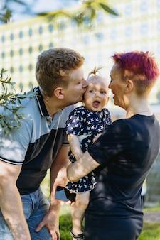 Kaukaski mężczyzna i kobieta rodzice małej dziewczynki całują swoją córeczkę