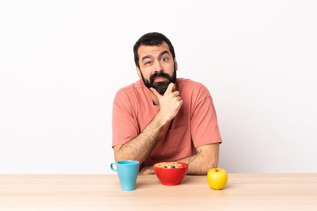 Kaukaski mężczyzna jedzący śniadanie w stole mający wątpliwości.