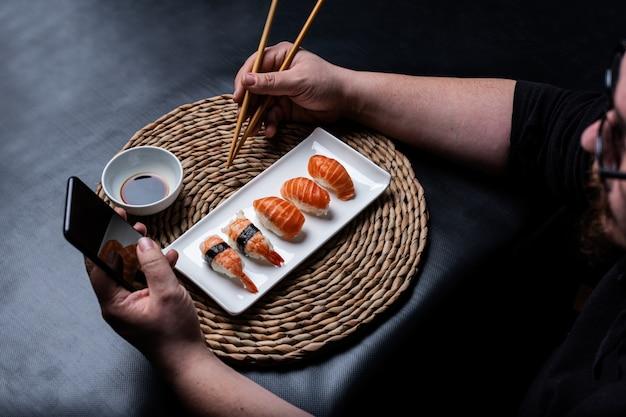 Kaukaski mężczyzna jedzenie sushi na wiklinowym obrusie patrząc na smartfona i pałeczkami w drugiej ręce na czarnym tle.
