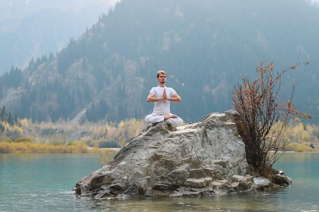Kaukaski mężczyzna jogi w medytacji na świeżym powietrzu, siedząc na samotnej wyspie skalnej górskiego jeziora.