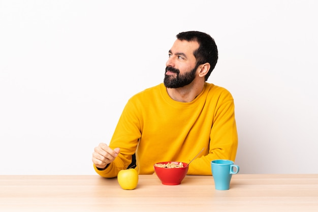 Kaukaski mężczyzna ma śniadanie w stole ma wątpliwości podczas gdy patrzejący stronę