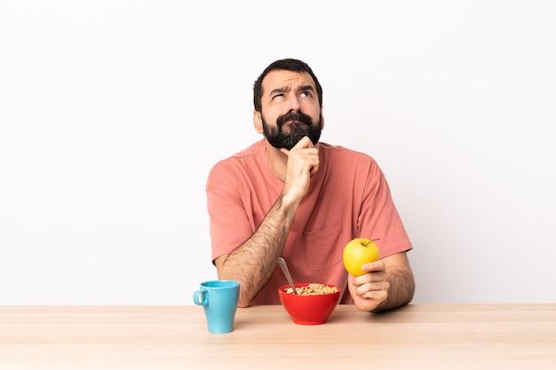 Kaukaski mężczyzna ma śniadanie w stole ma wątpliwości