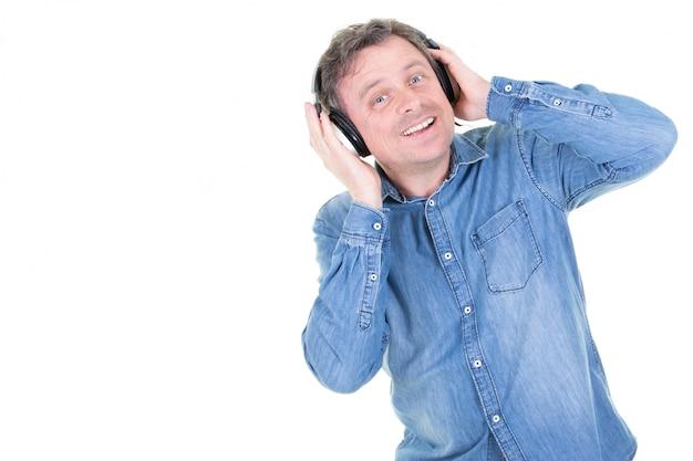 Kaukaski mężczyzna na białej ścianie, słuchanie muzyki w słuchawkach i taniec
