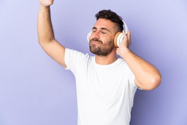 Kaukaski mężczyzna na białym tle na fioletowej ścianie słuchania muzyki i tańca