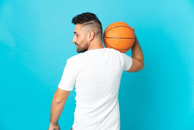 Kaukaski mężczyzna na białym tle na niebieskim tle gry w koszykówkę w tylnym położeniu