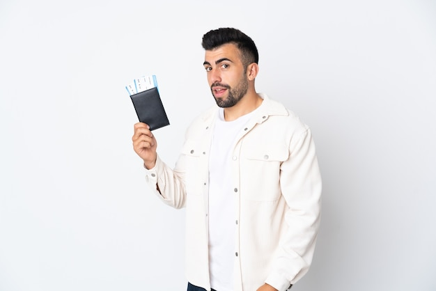 Kaukaski mężczyzna na białym tle szczęśliwy na wakacjach z paszportem i biletami lotniczymi