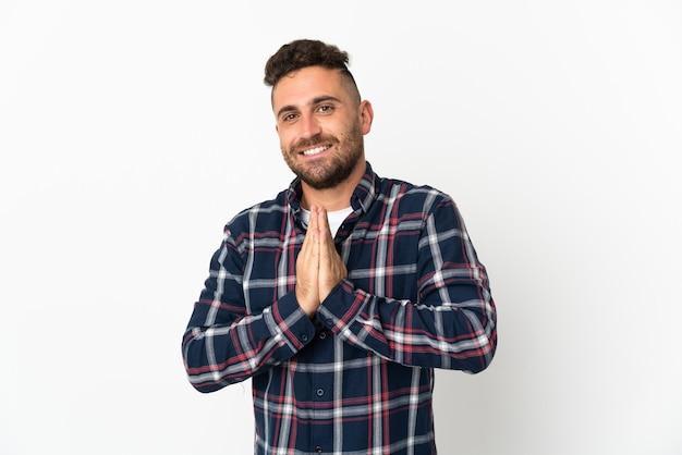Kaukaski mężczyzna na białym tle trzyma palmę razem. osoba o coś prosi