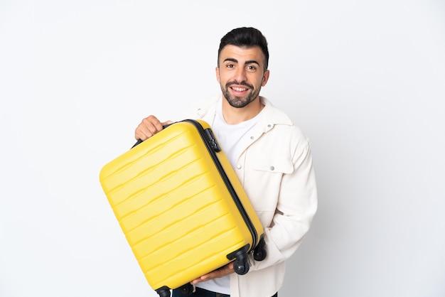 Kaukaski mężczyzna na białym tle w wakacje z walizką podróżną