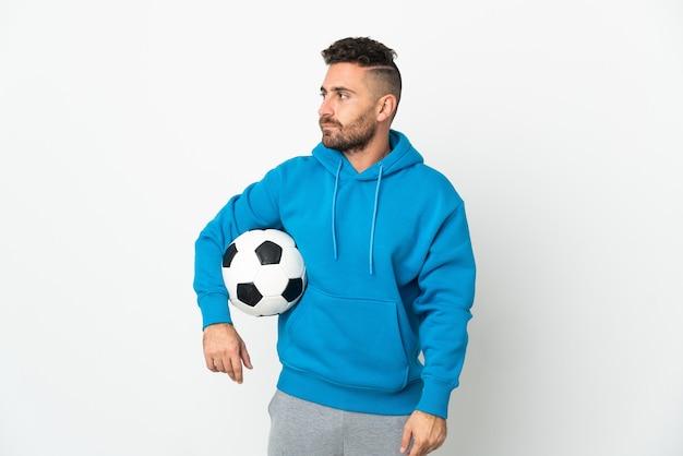 Kaukaski mężczyzna na białym tle z piłką nożną