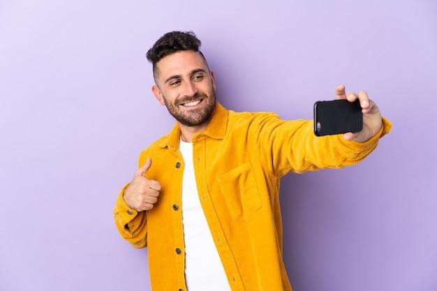 Kaukaski mężczyzna na fioletowym tle robi selfie z telefonem komórkowym