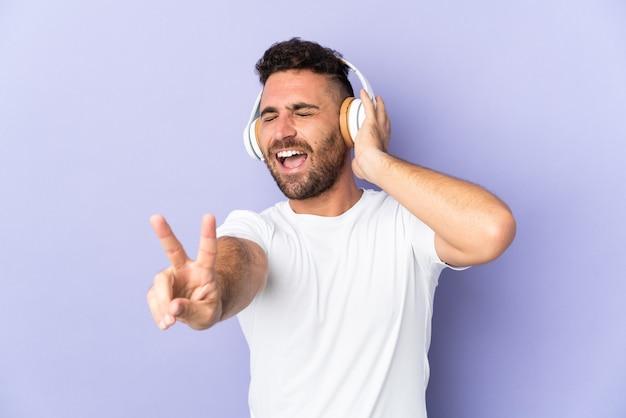 Kaukaski mężczyzna na fioletowym tle słuchania muzyki i śpiewu