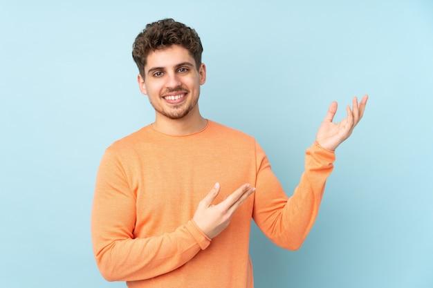 Kaukaski mężczyzna na niebieskiej ścianie wyciąga ręce w bok za zaproszenie