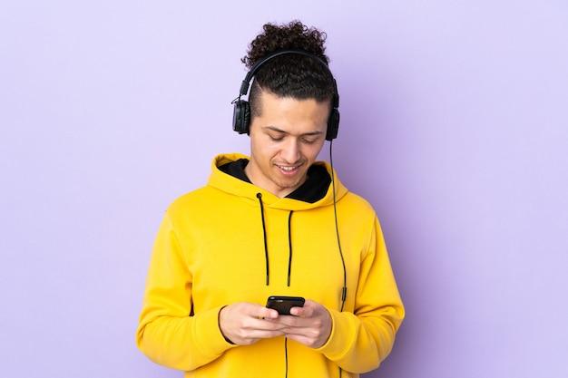 Kaukaski mężczyzna na pojedyncze fioletowe ściany słuchania muzyki i patrząc na telefon komórkowy