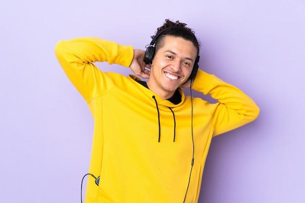 Kaukaski mężczyzna na pojedyncze fioletowe ściany słuchania muzyki