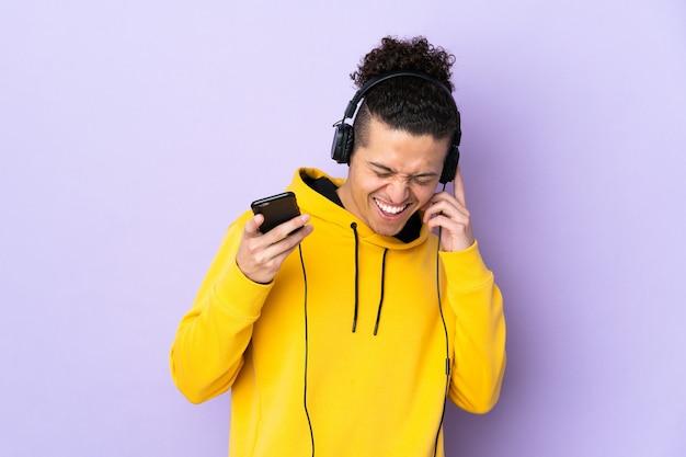 Kaukaski mężczyzna na pojedyncze fioletowe tło słuchanie muzyki z telefonu komórkowego i śpiewu