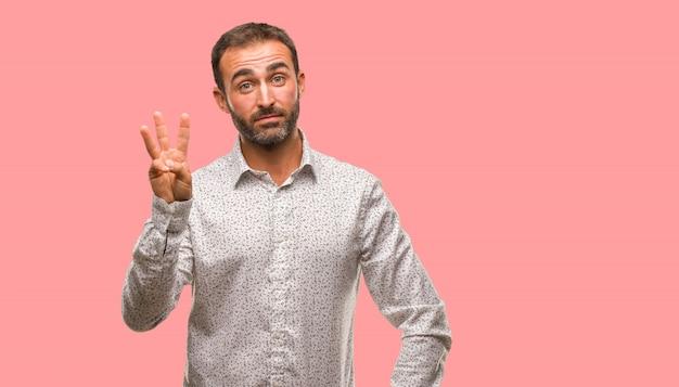 Kaukaski mężczyzna na szarym brackground pokazuje liczbę trzy