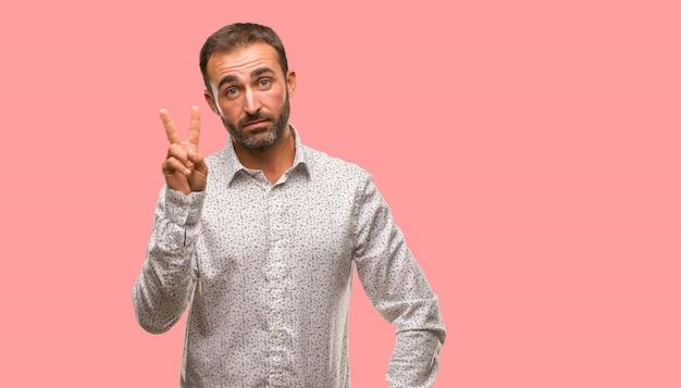 Kaukaski mężczyzna na szarym brackground pokazuje numer dwa