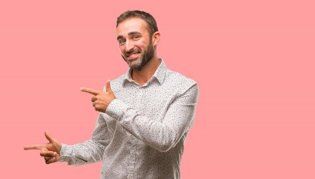 Kaukaski mężczyzna na szarym brackground wskazuje strona z palcem