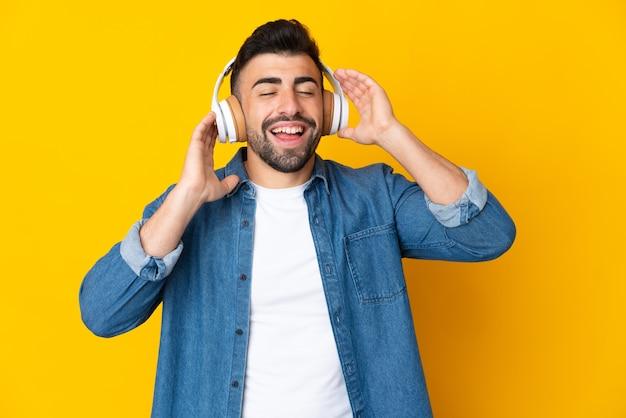 Kaukaski mężczyzna na żółto słuchanie muzyki i śpiewu